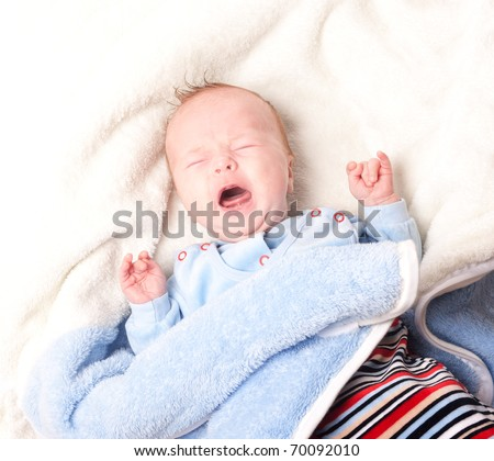 Crying newborn baby in bed