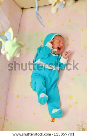 Crying newborn baby in the crib. He is lonely. Something bothers him. - stock photo