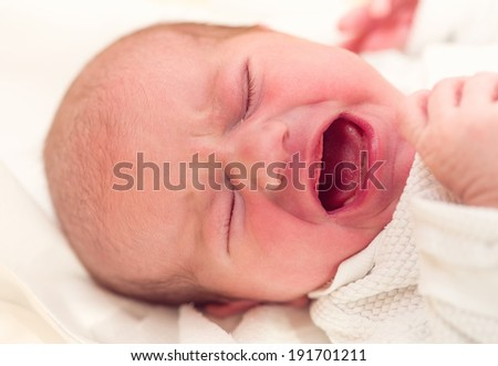 crying newborn baby in the hospital - the first hours of the new life - stock photo