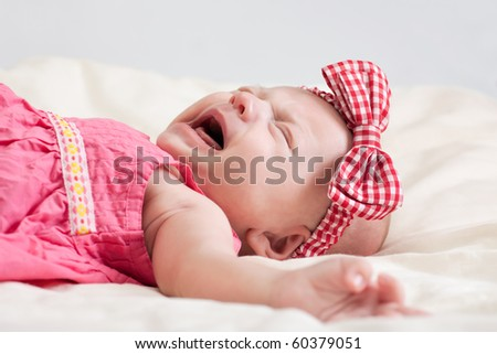 Crying ten weeks old baby girl on bed - stock photo
