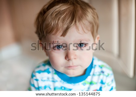 Crying toddler boy with blue eyes and blond hairs - stock photo