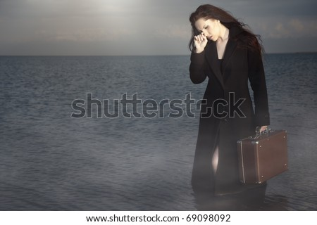 Crying woman in the wet coat holding her luggage and standing in the water. Natural fog and colors - stock photo
