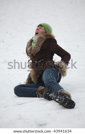crying woman lying in pain on the snowy road - stock photo