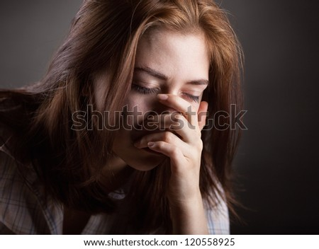 Crying woman on dark background - stock photo