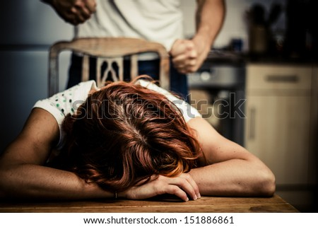 Crying woman with abusive partner behind her - stock photo