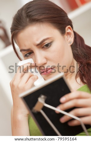 Crying woman with handkerchief on sofa looking at framed picture - stock photo