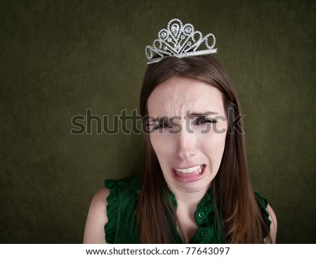 Crying young Caucasian woman with a tiara - stock photo