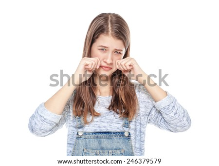 Crying young teenage girl in jeans overalls isolated  - stock photo
