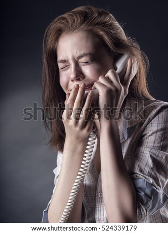Crying young woman with a phone on a dark background