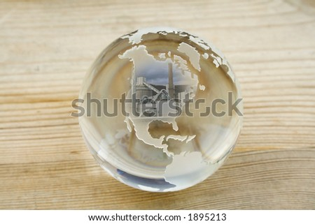 Crystal ball globe with factory over North America - stock photo
