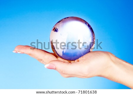 Crystal ball on hand. blue background - stock photo