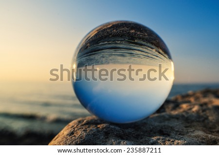 Crystal ball on the boulder at the sea - stock photo