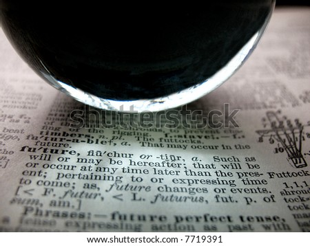 Crystal ball on 100 year old dictionary with the word future highlighted - stock photo