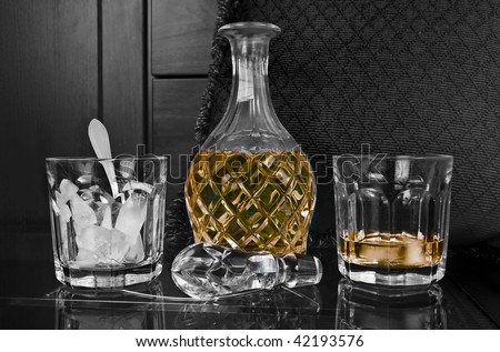 Crystal bottle and glass of old scotch with ice on a bar - stock photo