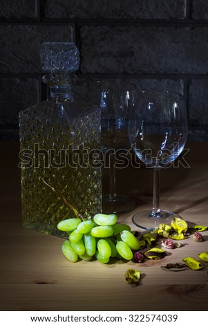 Crystal carafe of white wine, two glass, grapes on wooden table and gray bricks background - stock photo