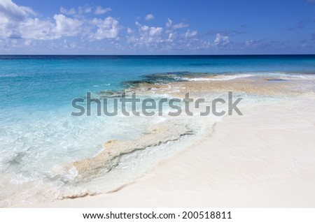 Crystal clear Caribbean waters inviting for a good swim (Half Moon Cay, The Bahamas). - stock photo