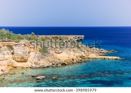 Crystal clear emerald water and rocky coastline of the Mediterranean Sea, Cyprus - stock photo