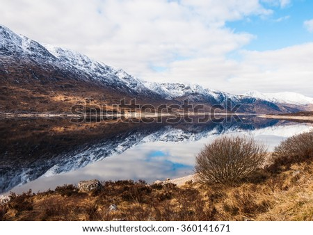 Crystal clear lake in scotland reflecting the icy mountains - stock photo