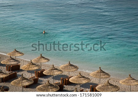 Crystal clear sea of Albania, with  wooden umbrellas and undefined swimmer - stock photo
