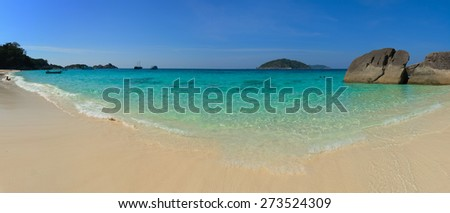 Crystal clear, tropical blue waters welcome tourists and excursionists on this sunny, white-sand beach in the Similan Islands of Thailand. - stock photo