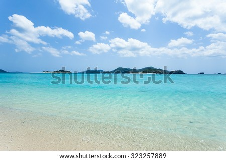 Crystal clear turquoise water lapping on white sand tropical beach, Zamami Island of the Kerama Islands National Park, Okinawa, Japan - stock photo