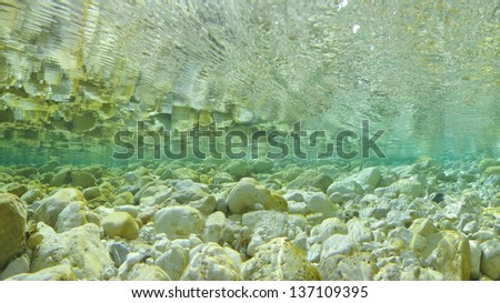 Crystal clear water at the river bottom - stock photo