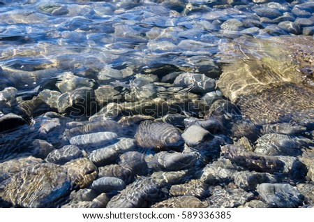Crystal clear water flows on pebble stones.