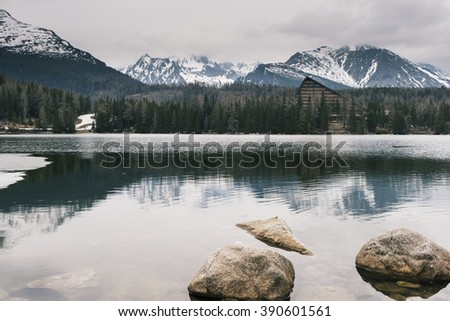 Crystal clear water of alpine lake and snow-capped mountains background - Strbske pleso, High Tatras, Slovakia - stock photo