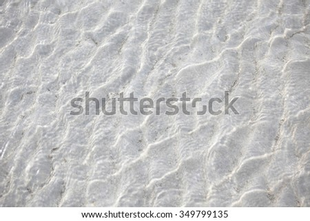 Crystal clear water over sand of the tropical sea - stock photo