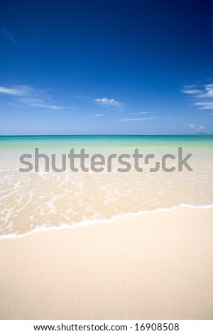 Crystal clear waters of the Andaman sea with soft white sand and clear blue sky. - stock photo