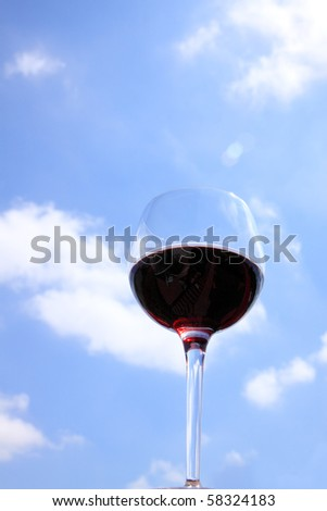 Crystal glass of deep red wine against bright blue cloudy sky - stock photo
