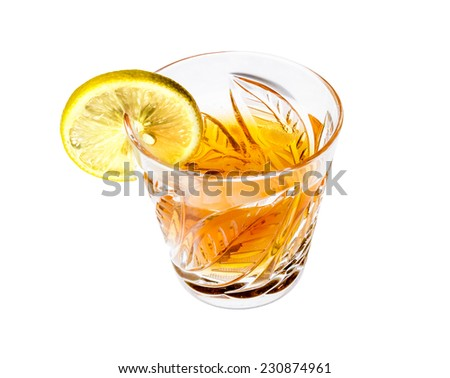 Crystal glass with alcohol and a slice of lemon, isolated on white background