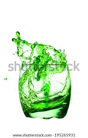 Crystal glass with green cocktail splashing on  white background .