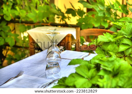 Crystal glasses are standing on a table with white table cloth in a restaurant framed with green plants - stock photo