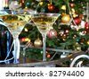Crystal glasses with wine bottle on the Christmas tree background - stock photo