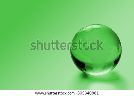 Crystal globe on green background - business and environmental concept - stock photo
