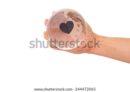 Crystal globe with Black heart in hand on White Isolate background - stock photo