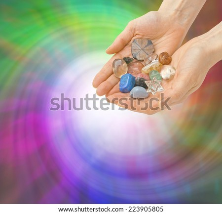 Crystal Healer and Energy Vortex - Crystal Healer with open palms cupped and holding a selection of healing crystals on a spiral green and purple colored swirling background - stock photo