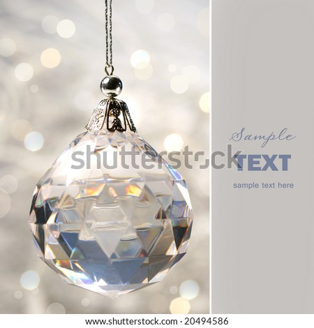 Crystal ornament hanging against shimmering background - stock photo