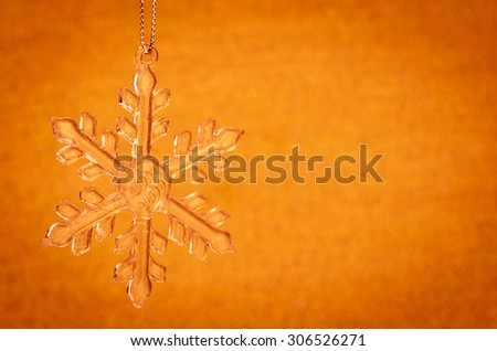 crystal snowflake decoration against orange background
