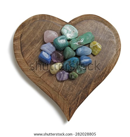 Crystal tumbled stones on wooden heart plaque - heart shaped wooden plaque with multicolored tumbled semi-precious stones laid on top on a white background - stock photo