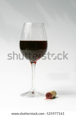 Crystal wine glass with red wine and cork with a bit of spilled wine