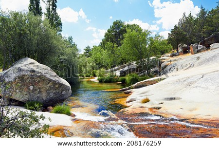"""Crystalline river flowing through huge rocks from mountain top. Tourist area """"La Pedriza"""" Madrid Spain. - stock photo"""