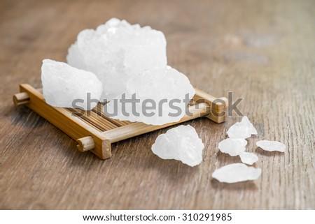 crystalline sugar on wooden pattern - stock photo