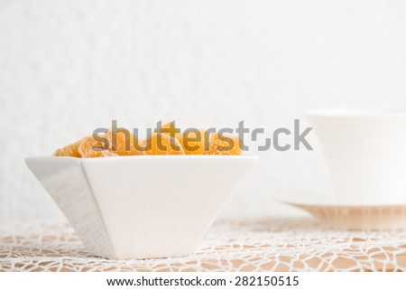 Crystallized ginger root  in white porcelain bowl and cup of tea on the background. Cup is cut. Shallow DOF. Close-up photo, horizontal - stock photo