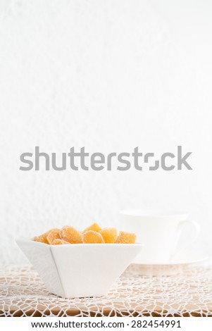 Crystallized ginger root  in white porcelain bowl and cup of tea on the background. Shallow DOF. Close-up photo, vertical - stock photo