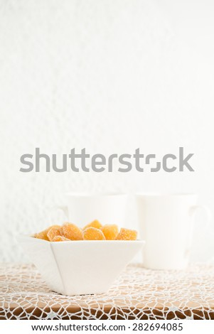 Crystallized ginger root  in white porcelain bowl and two tea mugs on the background. Shallow DOF, vertical - stock photo