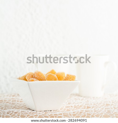 Crystallized ginger root  in white porcelain bowl and two tea mugs on the background. Shallow DOF, square - stock photo
