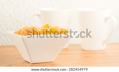 Crystallized ginger root  in white porcelain bowl and two tea mugs on the wooden background. Shallow DOF. Close-up photo, horizontal - stock photo