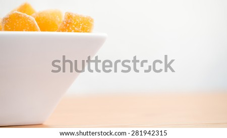 Crystallized ginger root  in white porcelain bowl. Bowl is cut vertically. Shallow DOF. Close-up photo, wide screen - stock photo
